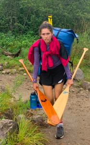 Image description: Georgia is carrying a huge bag, 2 paddles and 2 water bottles through the woods and looks unhappy