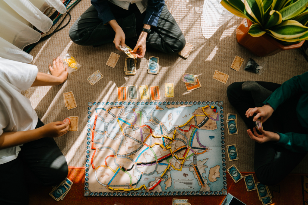 Image description: Group of people playing a board game on the floor