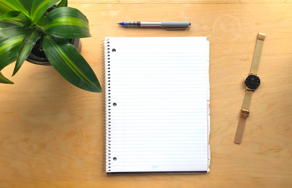 Photo of a desk with a plant, pen, notebook and watch on it