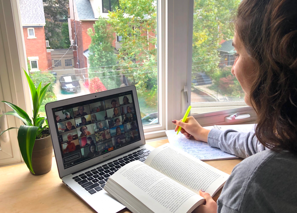 Photo of a girl holding a book and a highlighter who is sitting at a desk and taking part in an online grad writing group