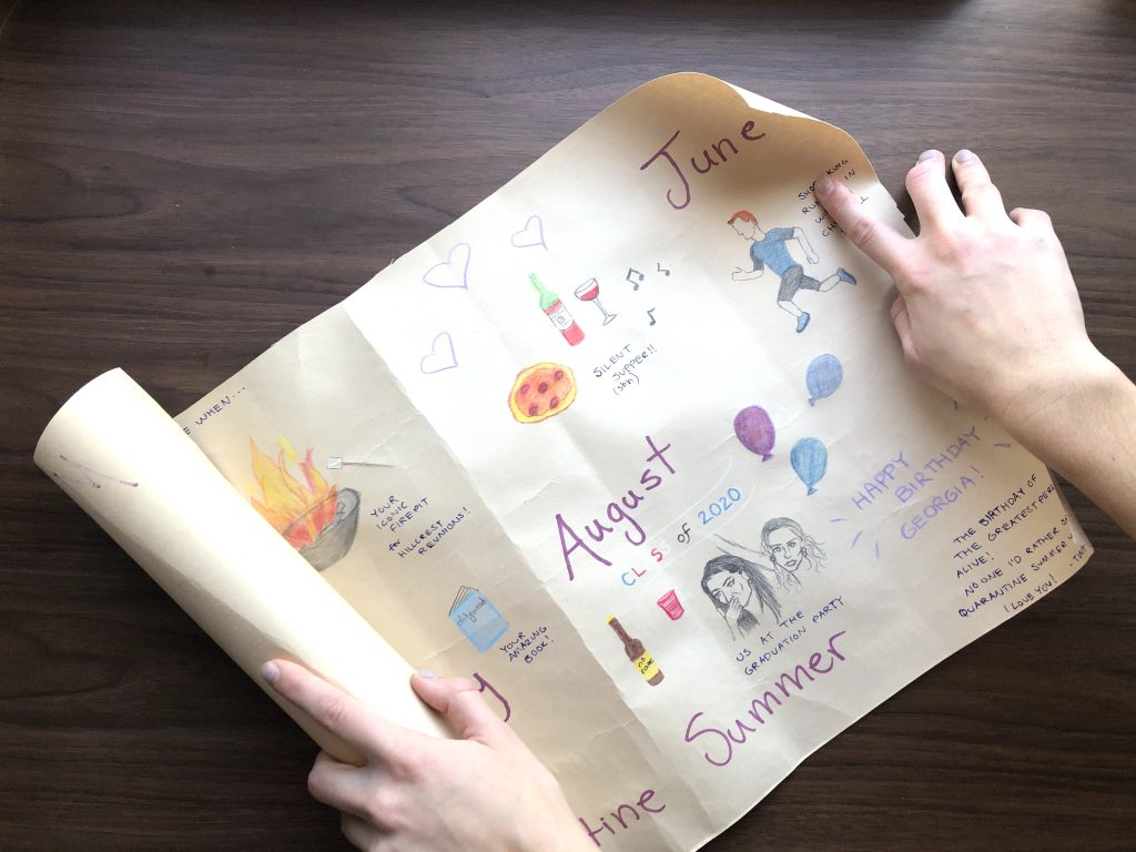 two hands are unrolling a large, colourful card that has the months written out and pictures drawn around them