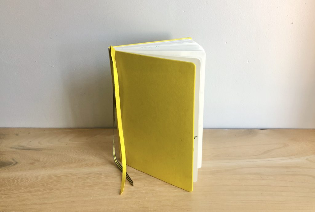 a yellow notebook standing up on its side