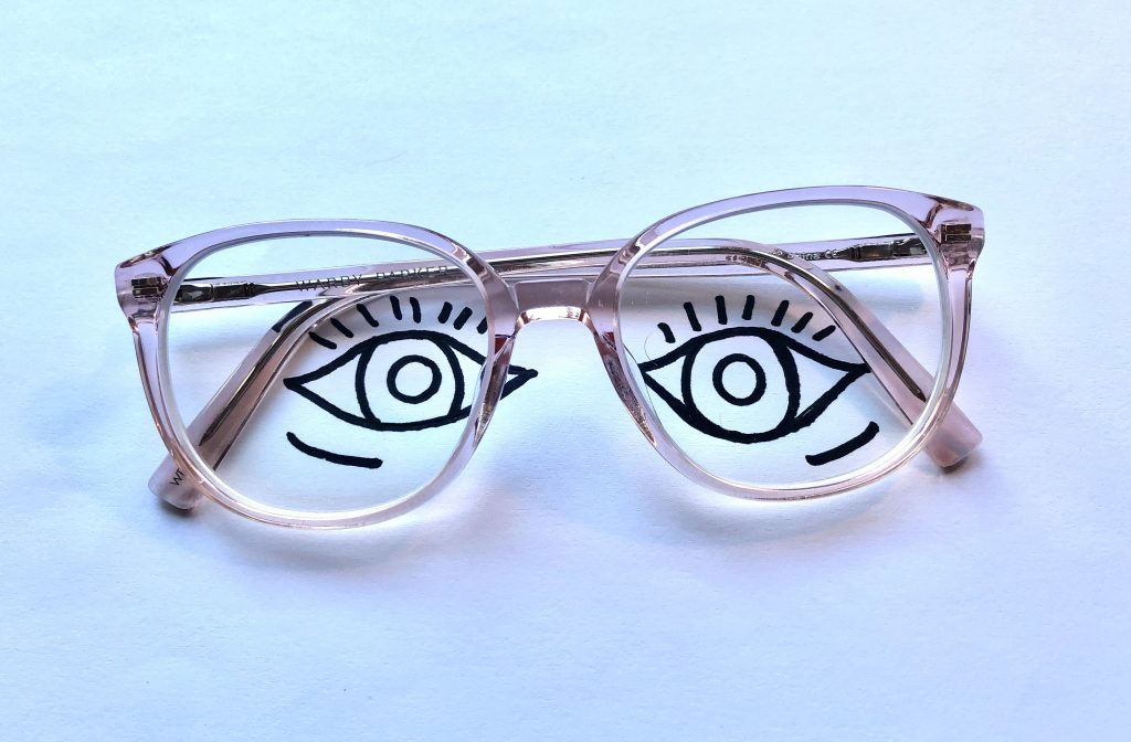 eyes drawn onto a piece of paper with pink glasses sitting on top