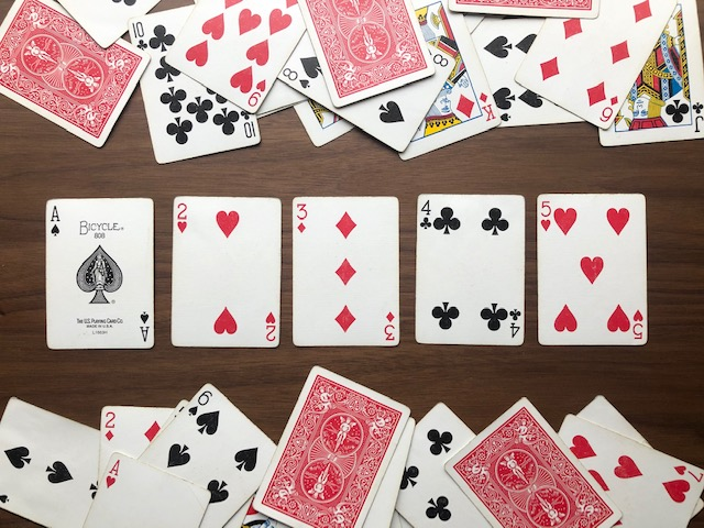 a jumble of cards with five organized in the middle of the table