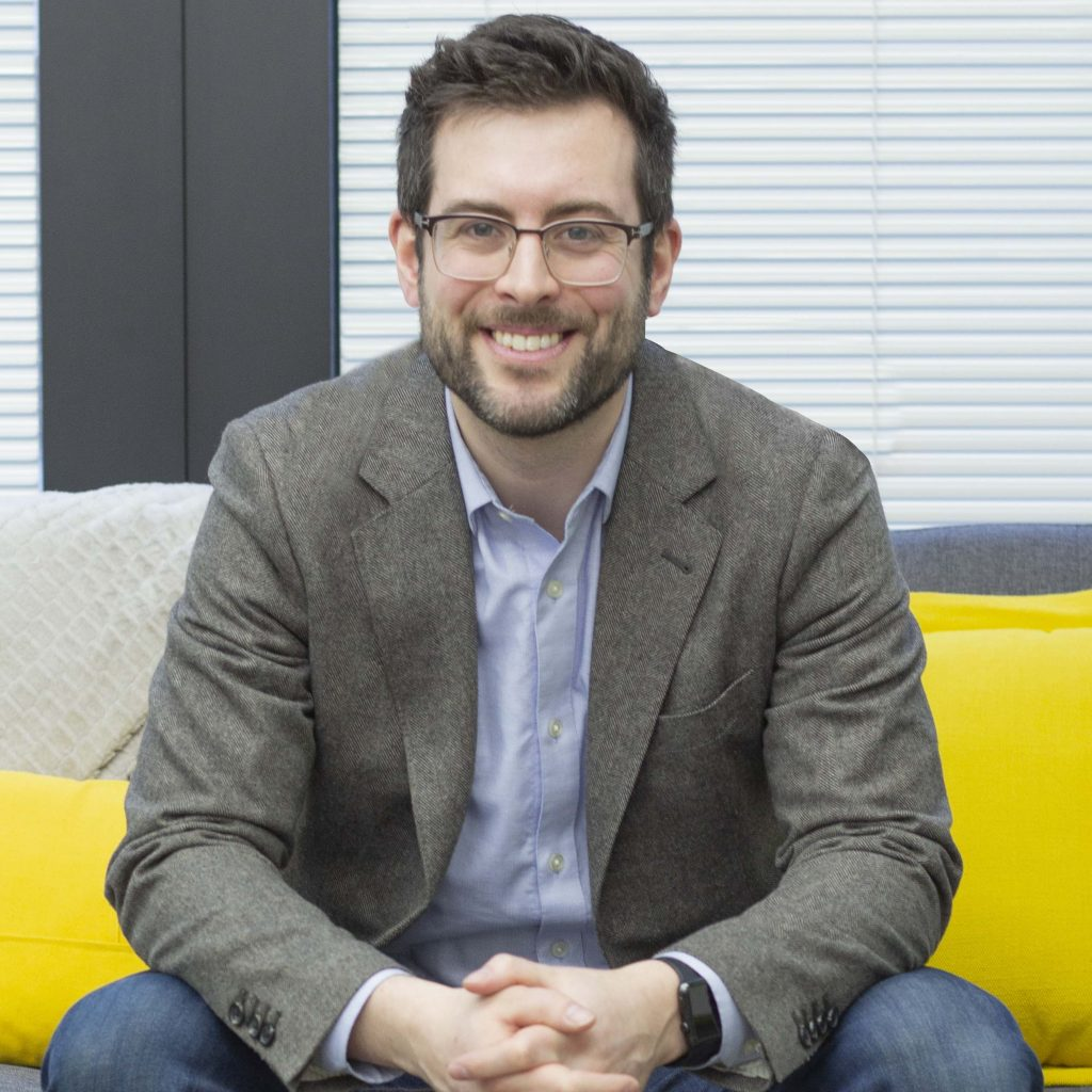 photo of Dr. Ryan Kealey, who is sitting on a couch and smiling