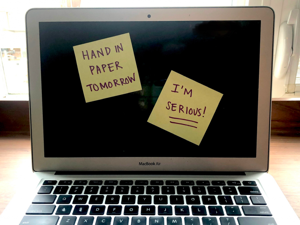 """an open laptop that has two sticky notes attached to the screen. One reads """"Hand in paper tomorrow"""" the other reads, """"I'm serious!"""""""