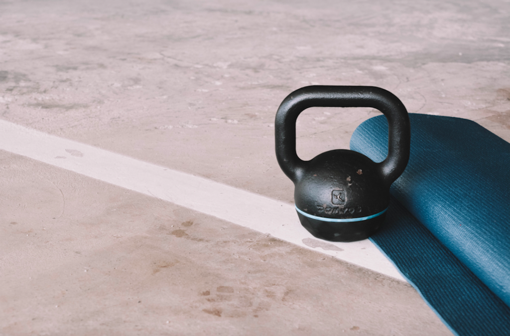 photo of a kettle bell and rolled up yoga mat on the ground