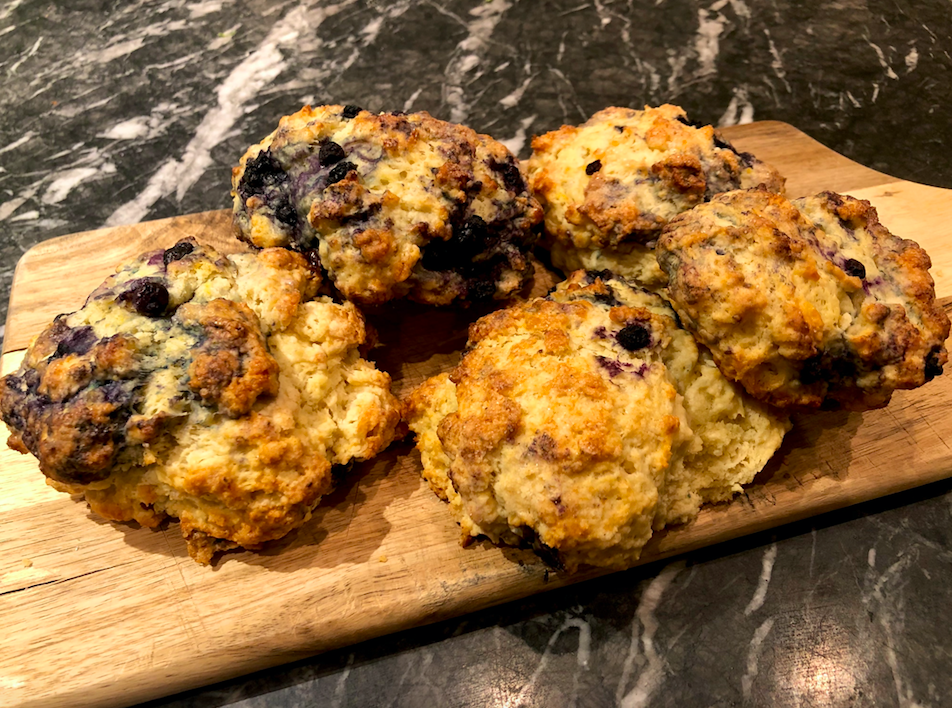 Photo of five blueberry scones arranged on a cutting board which is on top of a black marble counter