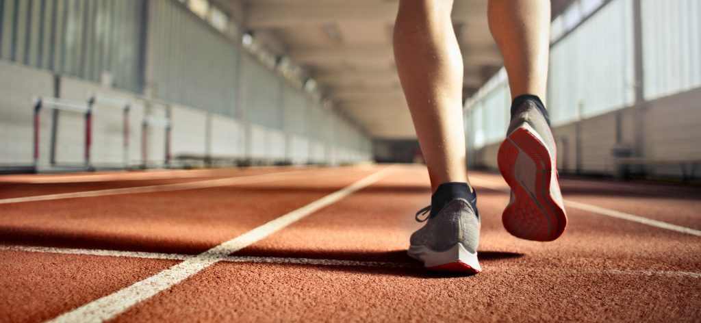 close-up photo of feet in running shoes walking along a track