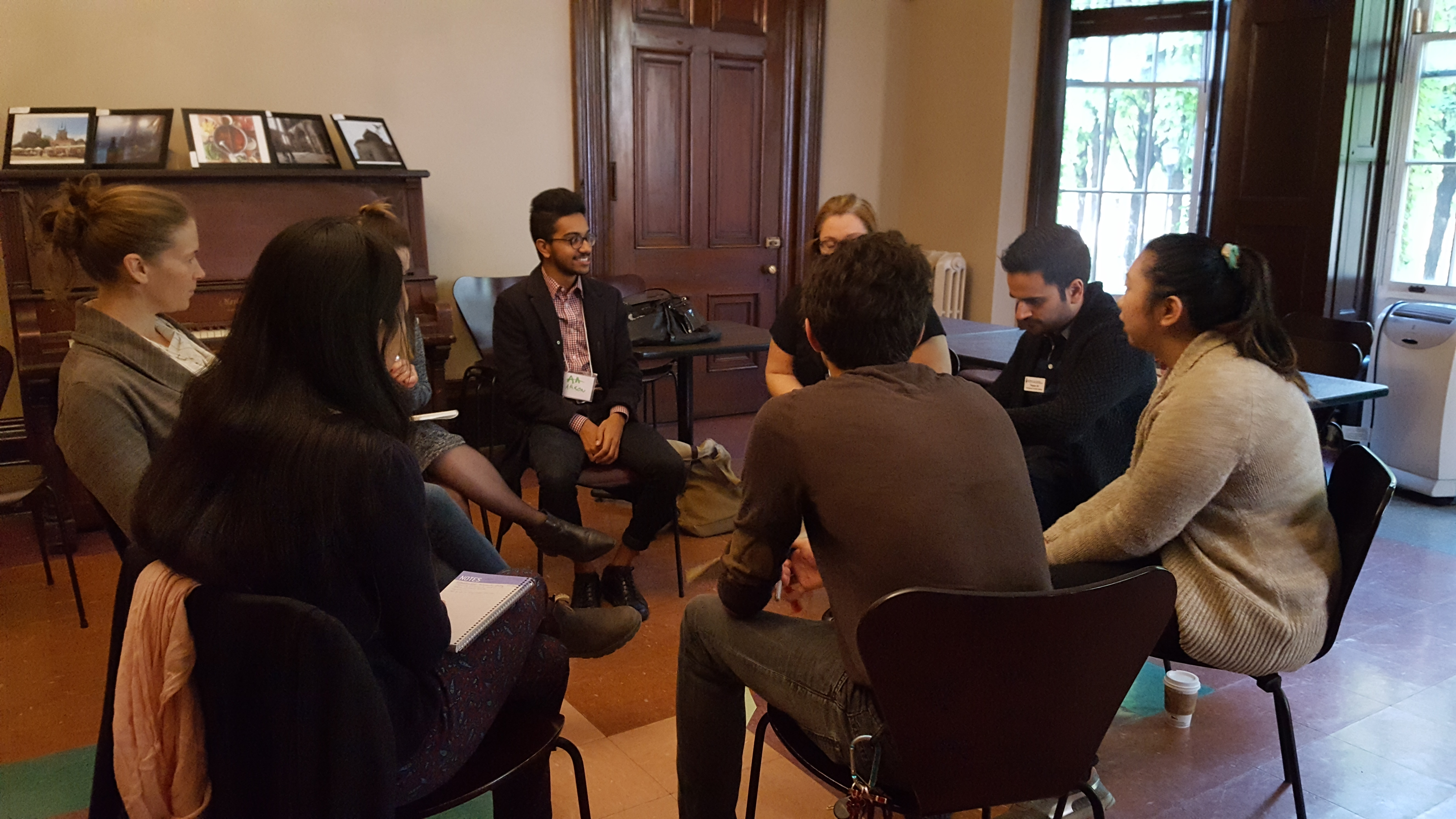 staff and students seated in a circle engaged in discussion