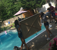 Students setting up in front of a pool