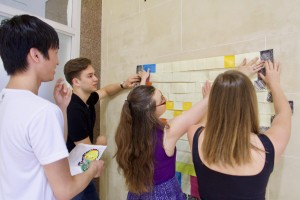 Four students posting colourful sticky notes on the wall