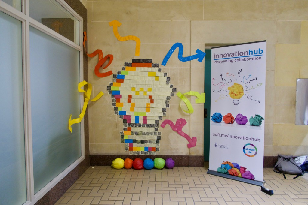 An Innovation Hub banner alongside an art installation consisting of coloured sticky notes arranged into the shape of a lightbulb with arrows emerging from it.