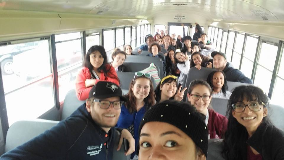 Group photo of smiling students on a school bus