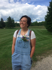 Smiling young person with short hair and glasses in overalls standing in a field