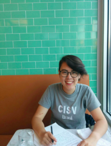 Smiling young woman with short brown hair and glasses sitting at a booth