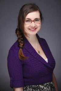Headshot of smiling young woman with brown hair and glasses in a purple top