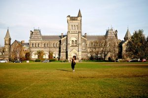 Student walking on grass in front of university building