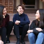 Three students sitting on steps, talking and laughing