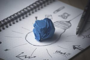 Crumpled ball of blue paper on top of black and white notebook page with doodles on it