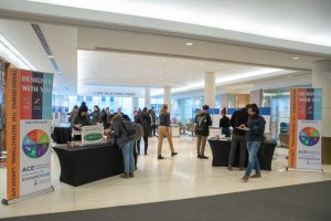 An event space that has students walking around ,attending booths for activities and information.
