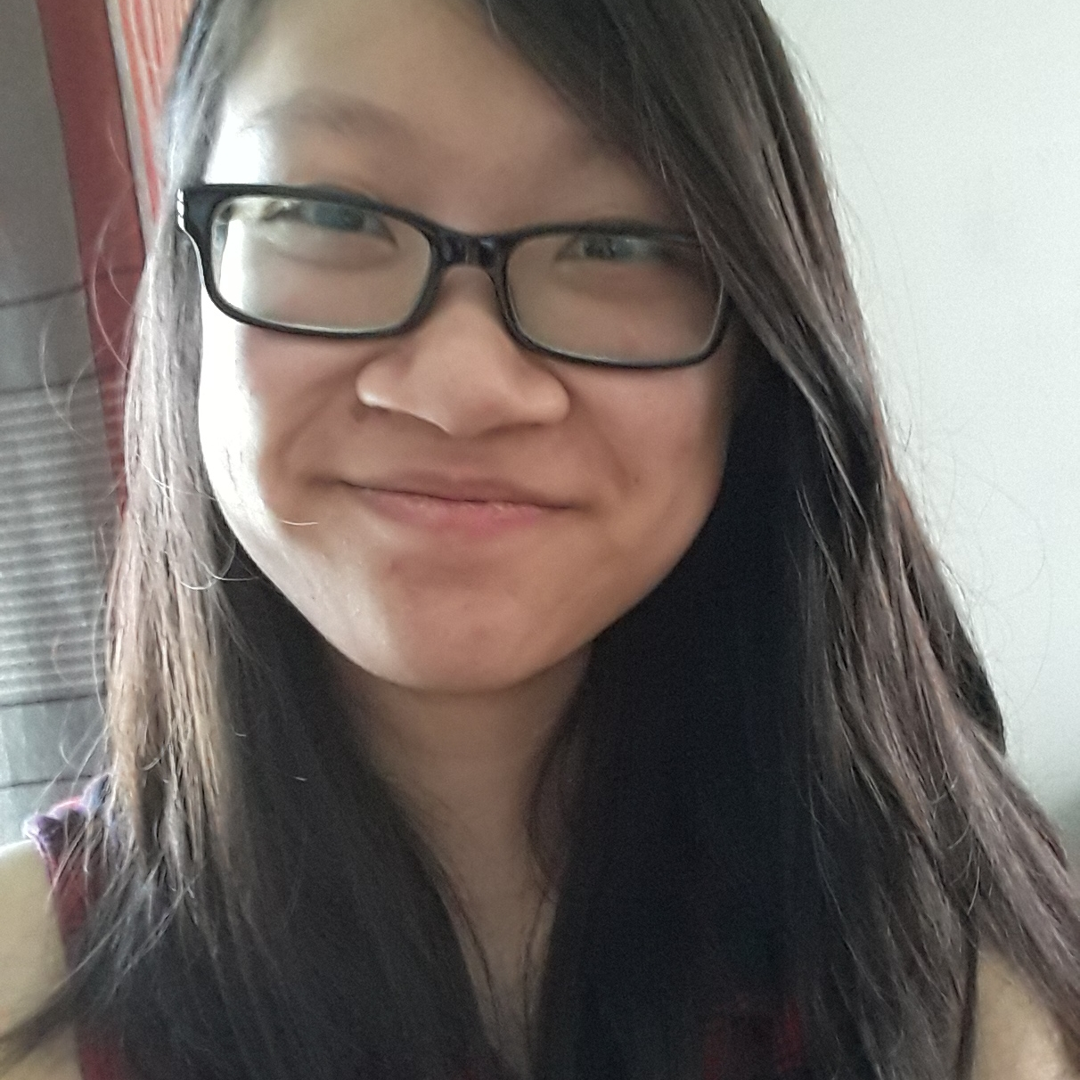Felicia is smiling at the camera, wearing dark rimmed glasses and has long brown hair.