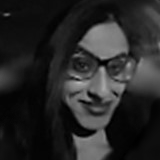 A black and white photo of Nadhiena, smiling to the camera and wearing glasses