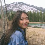 A photo of Nhi looking towards the camera. They are outside, with mountains and trees in the background.