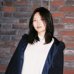 Peiyu is wearing a white shirt with a black coat, standing in front of a colourful brick wall.