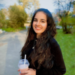 Ritika is standing outside, wearing a black top, smiling towards the camera. Its sunny and theres trees and a road in the background.