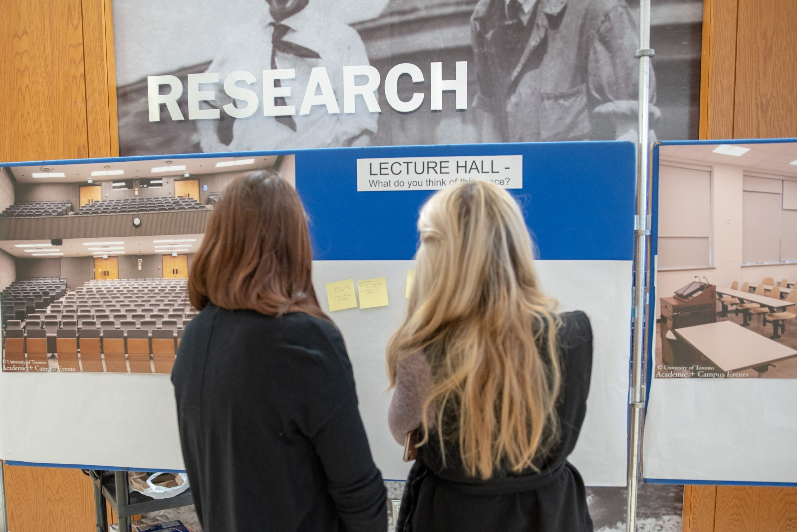 """Two students looking at a board that reads """"Research"""", with writing materials & photos underneath"""