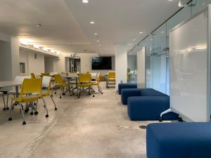 A open, brightly lit room with moveable furniture and white boards along the side.