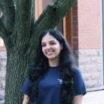 Sanksriti is wearing a blue shirt, standing outside