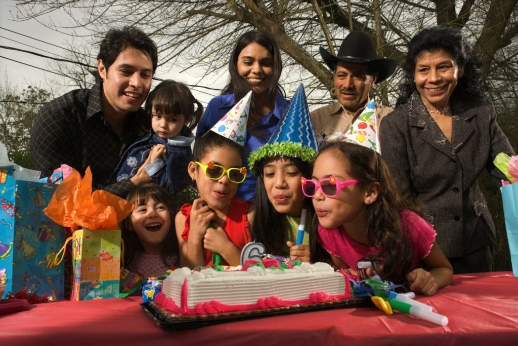 Four young children blowing out birthday candles with parents and grandparents standing behind them, in a park.