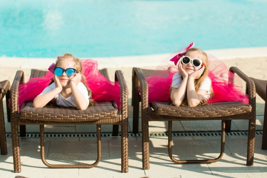 Two girls sitting down in pink tutus with sunglasses.