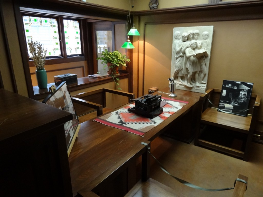 Image of well lit office with type writer and art on walls