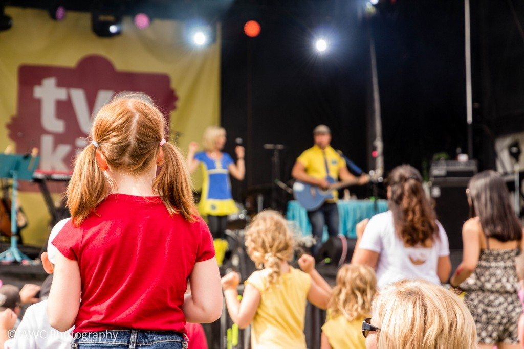 Image of child standing, looking onto TVO Kids stage where musicians are performing