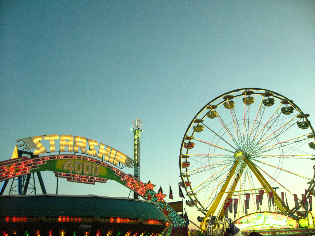 Image of ferris wheel and starship play area lit up against dusky sky