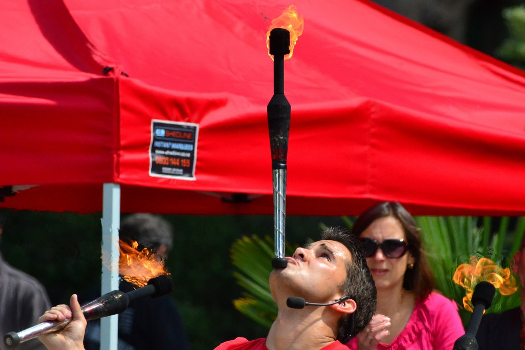 Image of busker balancing flaming baton on chin