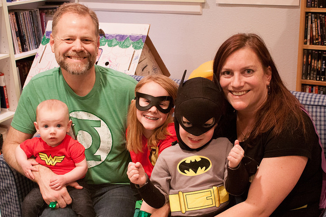 Image of parents and three kids sitting on sofa in superhero t-shirts and masks.