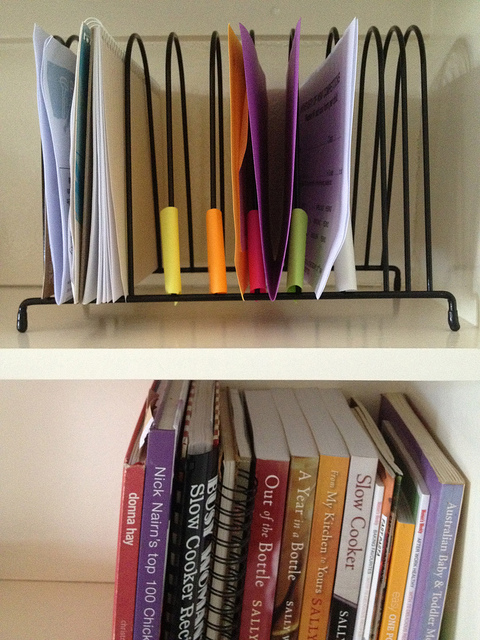 Image of wire file organizer on shelf above stacked books.