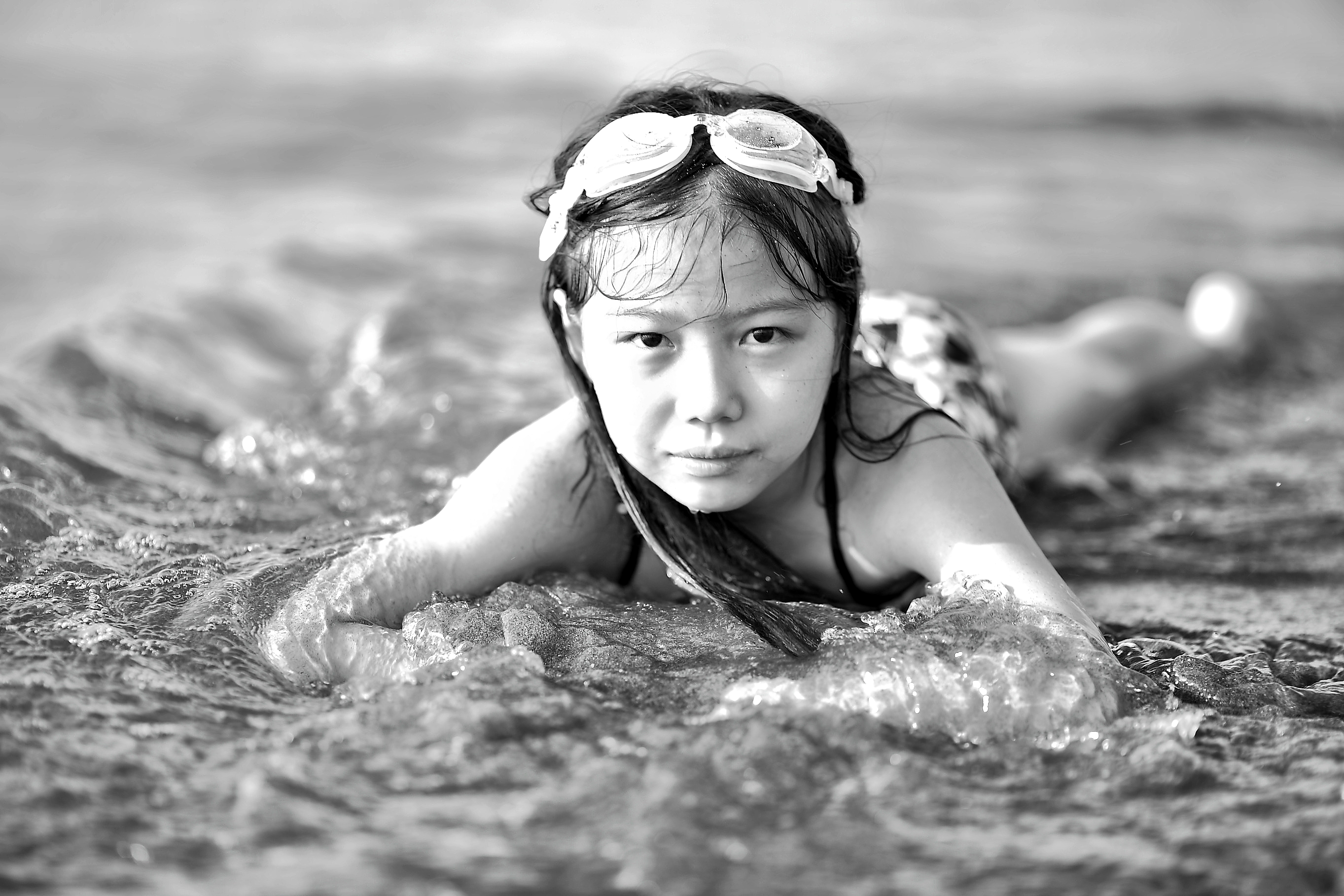 Youth in goggles lying in shallow water