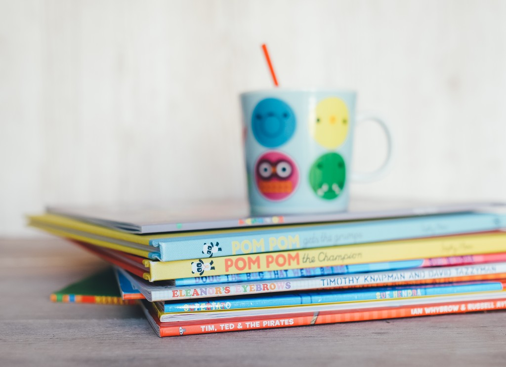 Image of child's mug atop of pile of children's books.