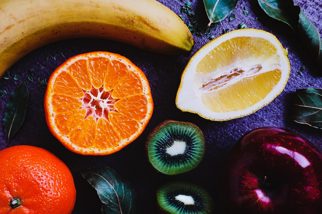 Image of sliced fruits on a wooden table- kiwi, orange, banana, lemon