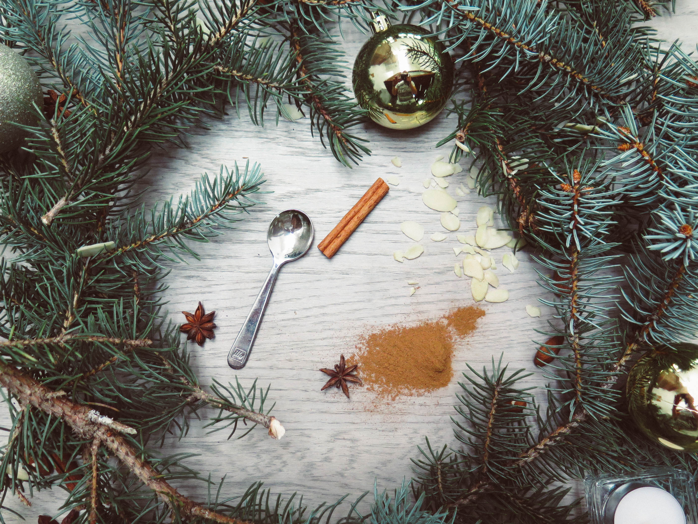 Spoon, cinnamon stick, and ground nutmeg centered in an evergreen wreath