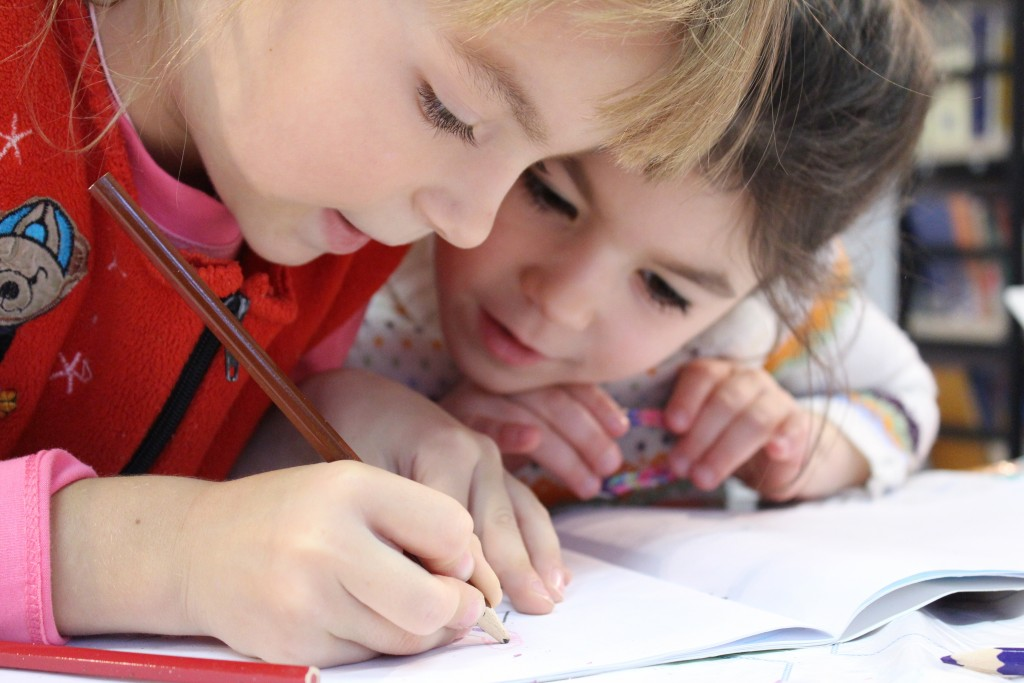 Two children leaning over notebook, drawing