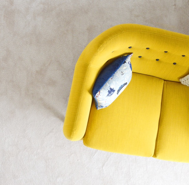 Yellow sofa with gray pillow pictured from birds eye view.