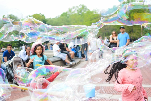 Children running through huge bubbles outside