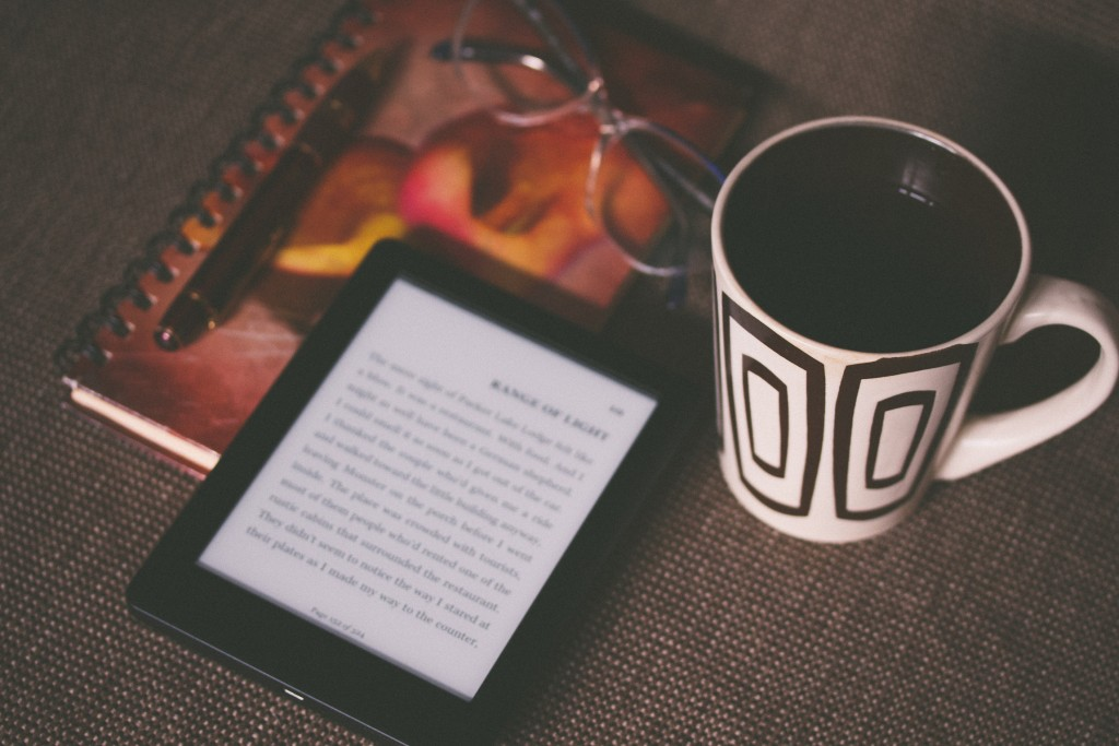 E-reader atop of colourful notebook with eyeglasses and ceramic mug beside it.