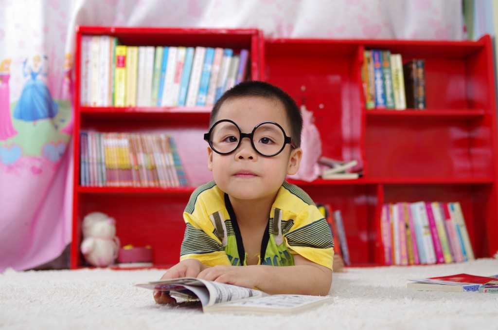 Image of child wearing large circular glasses reading a book infront of a large red bookshelf